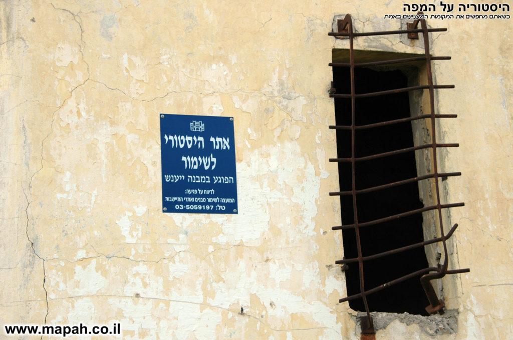 שלט כחול המועצה לשימור על קיר משטרת באטאני - צילום: אפי אליאן
