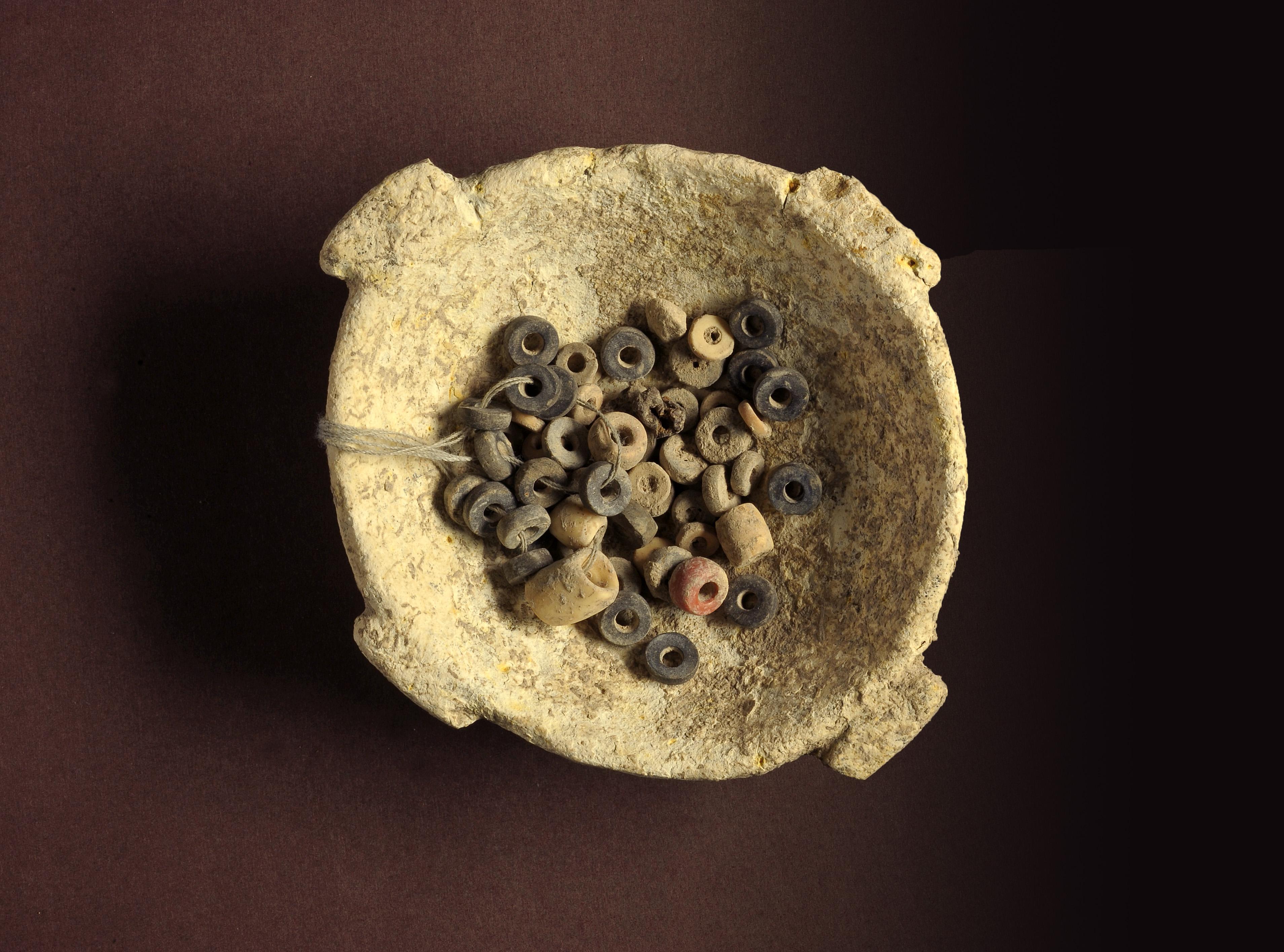 קערת אבן ובה חרוזים עתיקים שנמצאו בחפירות בעין ציפורי - צילום: קלרה עמית, רשות העתיקות