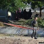 """קבוצת סקרנים לצד שוטר מג""""ב ליד הבניין הפגוע בקרית מלאכי"""