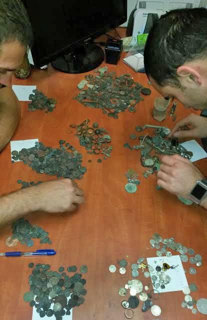 אנשי רשות העתיקות בוחנים את הפריטים שנמצאו בבית החשוד בשוד העתיקות - צילום: היחידה למניעת שוד ברשות העתיקות