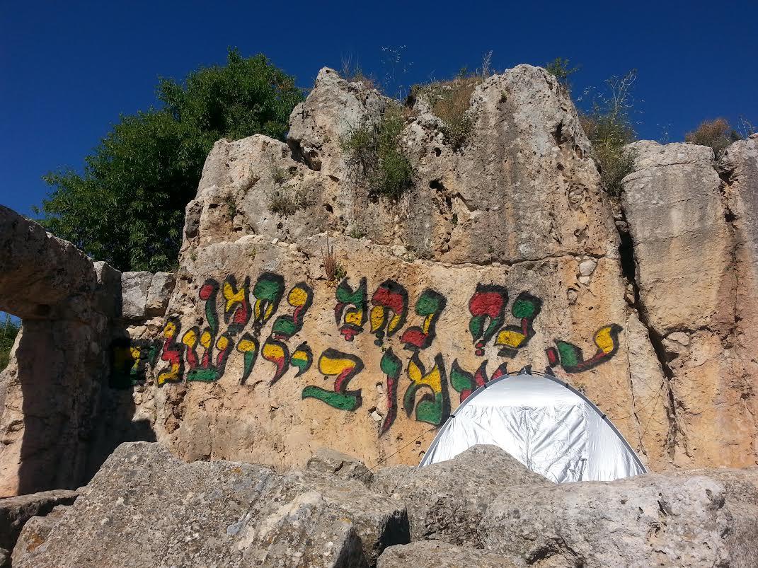 כתובת הגרפיטי שרוססה בבית הכנסת העתיק במירון - צילום: אורי ברגר