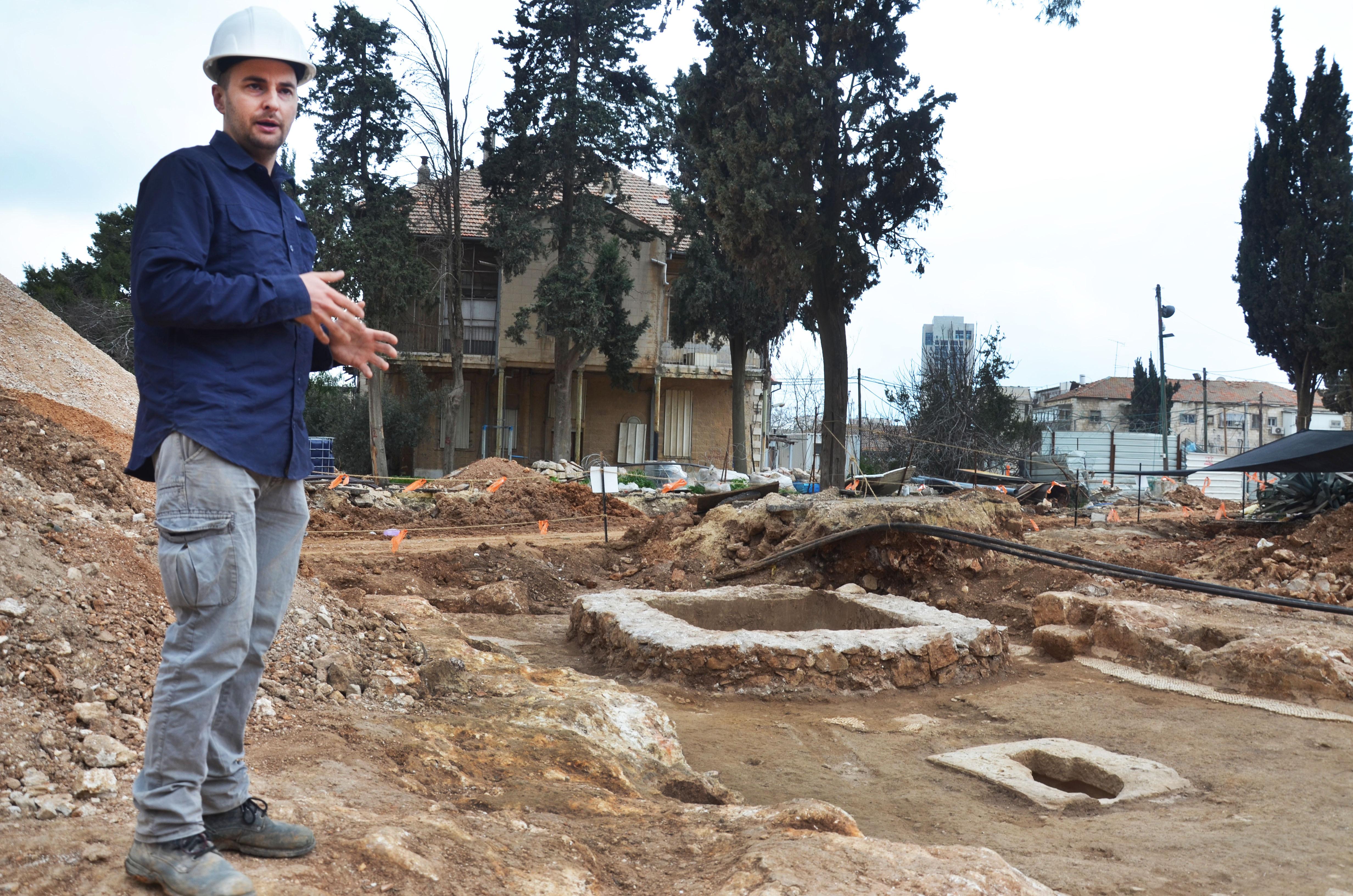 . מנהל החפירה, אלכס ויגמן, לצד בית הגתות המשוכלל. יתכן שהפיקו בו יין בטעמים. צילום: באדיבות רשות העתיקות