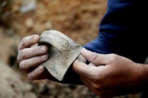 """טביעת חותם על ידית קנקן """"למלך חברן"""" בעת חשיפתה בשטח– צילום: יולי שוורץ"""