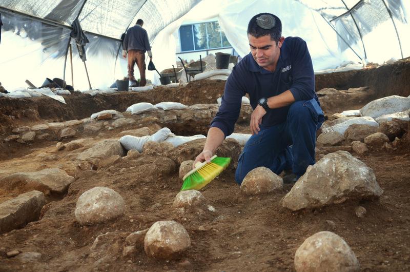כפיר ארביב, מנהל החפירה מטעם רשות מהעתיקות, מנקה את אחת מאבני הקלע. צילום: יולי שוורץ