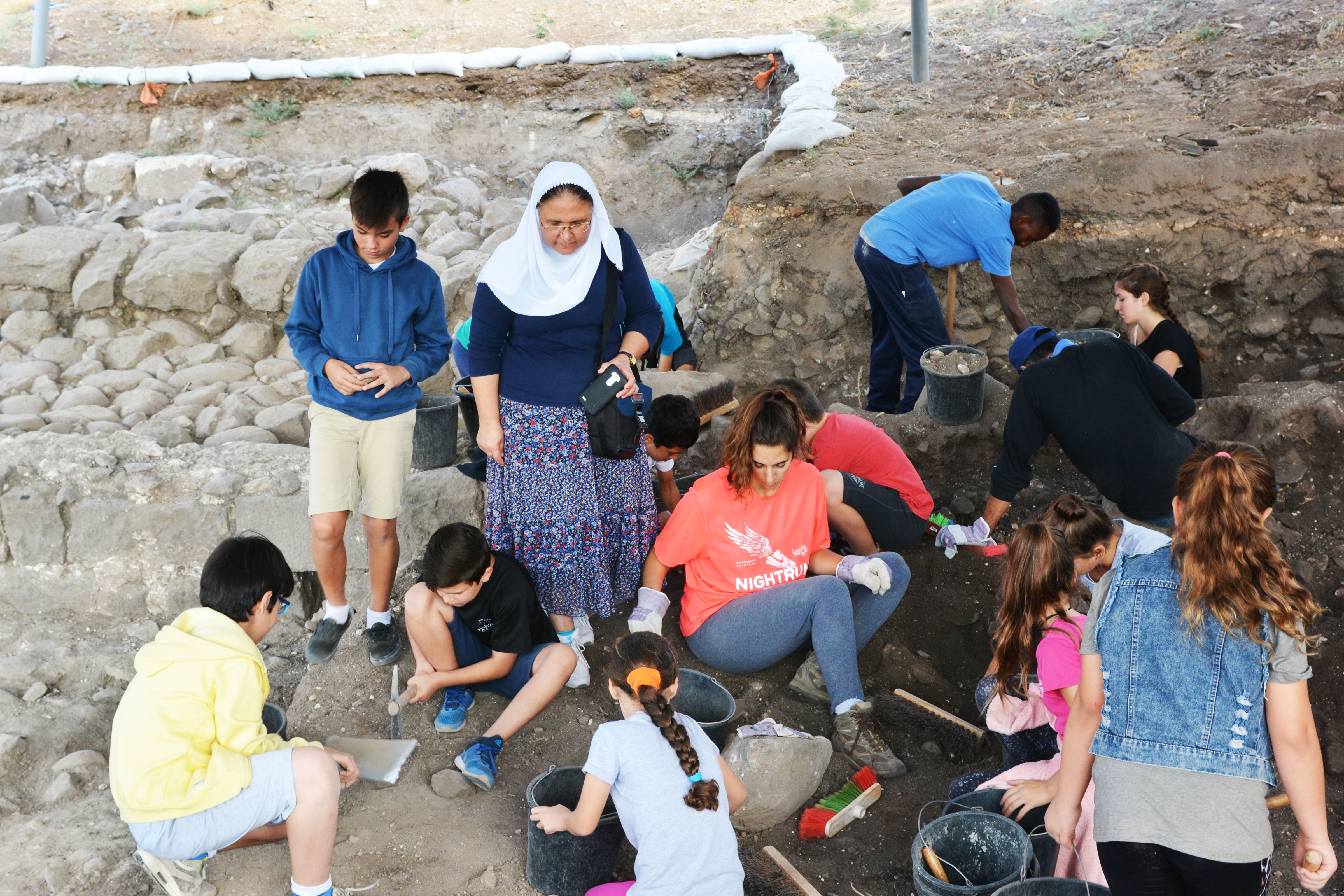"""ילדי בית ספר """"תינאל"""" בכפר כמא עם המורה סילביה אישליין, מתנסים בעבודת הארכיאולוגים. צילום: גלעד צינמון"""