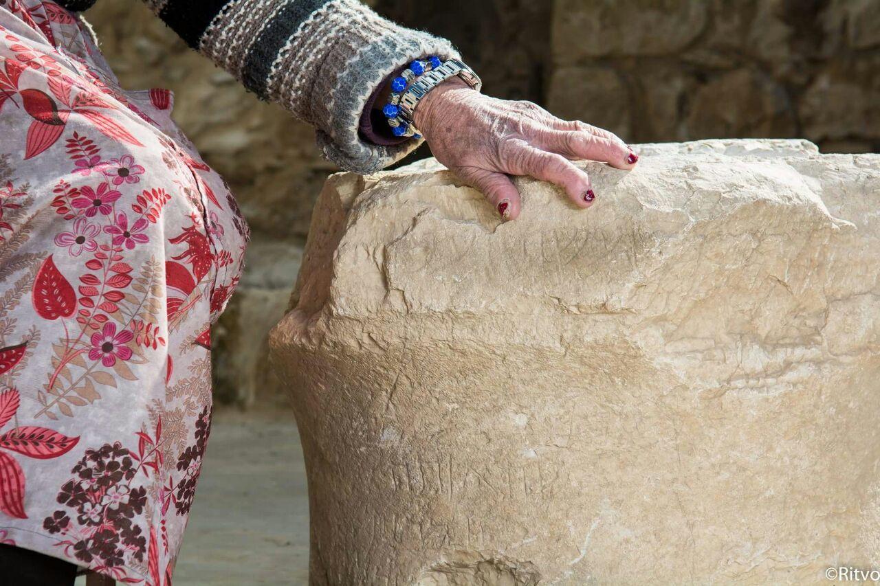 ידה של מרגלית זינאתי מהכפר פקיעין מונחת על האבן העתיקה. צילום: Ritvo, באדיבות בית זינאתי