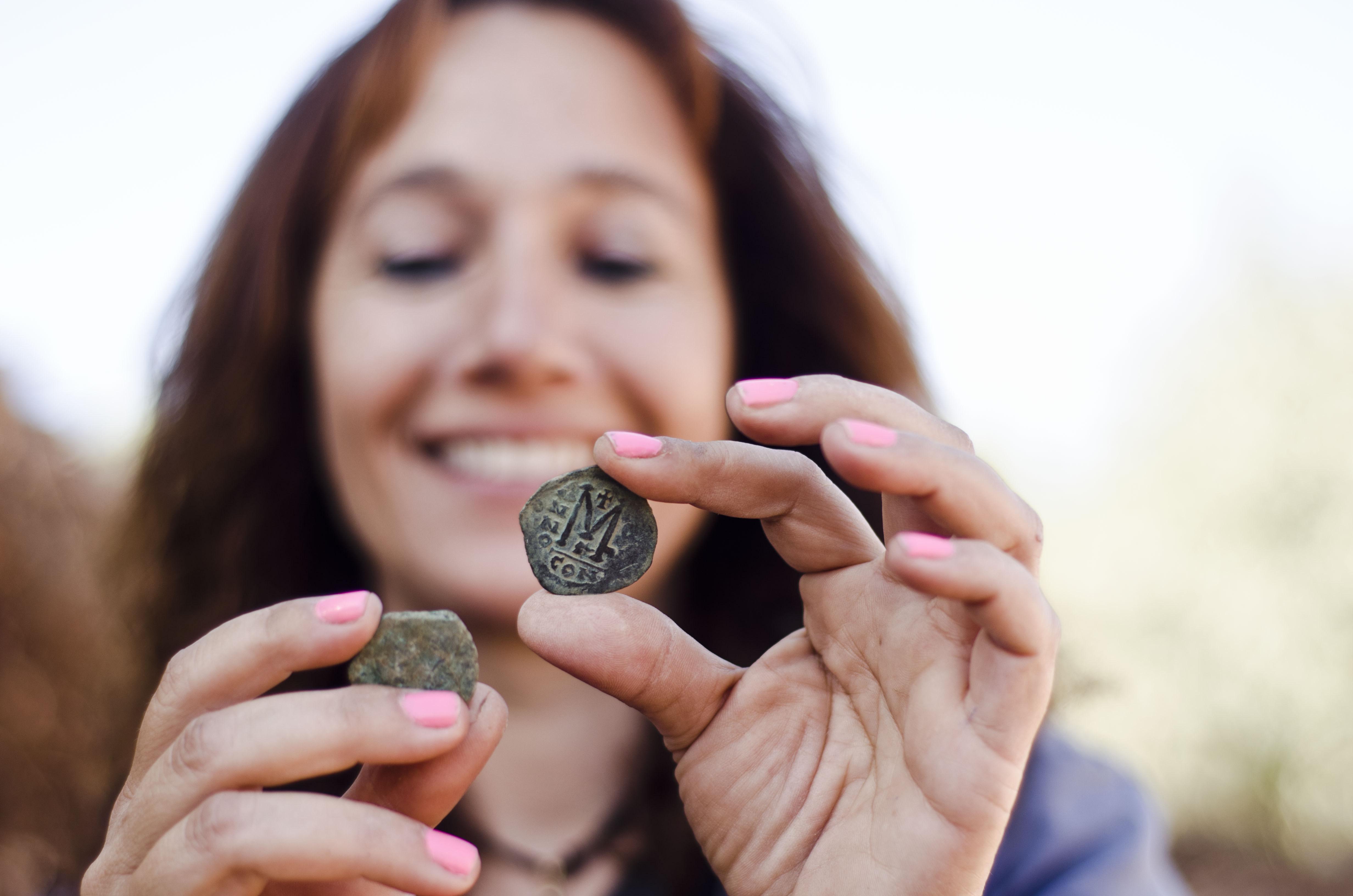 אנט נגר, מנהלת החפירה מטעם רשות העתיקות, עם אחד המטבעות. צילום: יוֹלי שוורץ