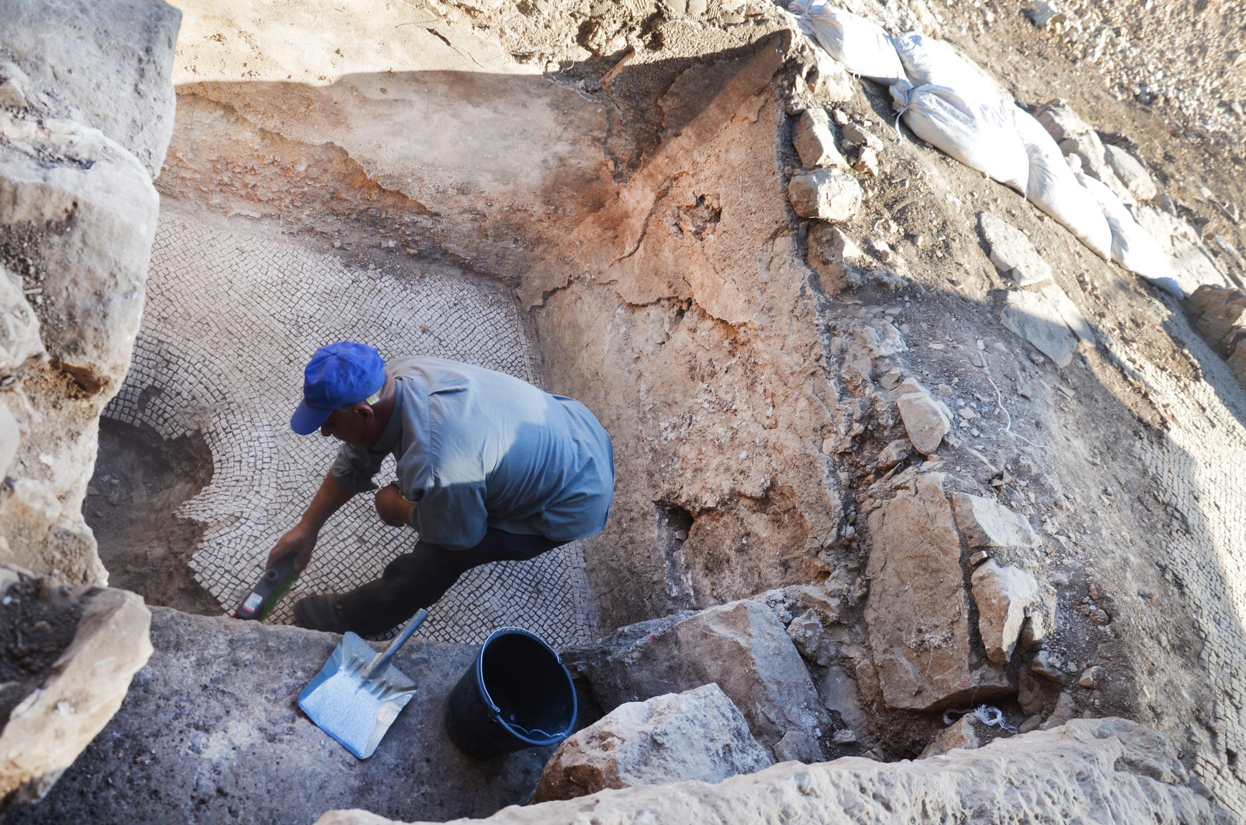 עובד בחפירה מנקה בור איגום של גת שנחשפה באתר. צילום: יוֹלי שוורץ