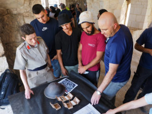 """חניכי מכינת """"מלח הארץ"""" ונציגי רשות העתיקות מציגים את הממצאים שחשפו בפני הנספחת הצבאית בשגרירות בריטניה בישראל, קולונל רוני ווסטרמן"""