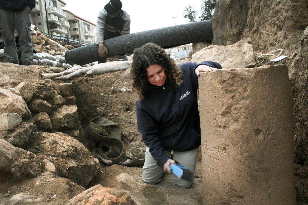 דנית לוי, מנהלת החפירה מטעם רשות העתיקות, ליד הכתובת כפי שנמצאה בשטח. צילום: יוֹלי שוורץ