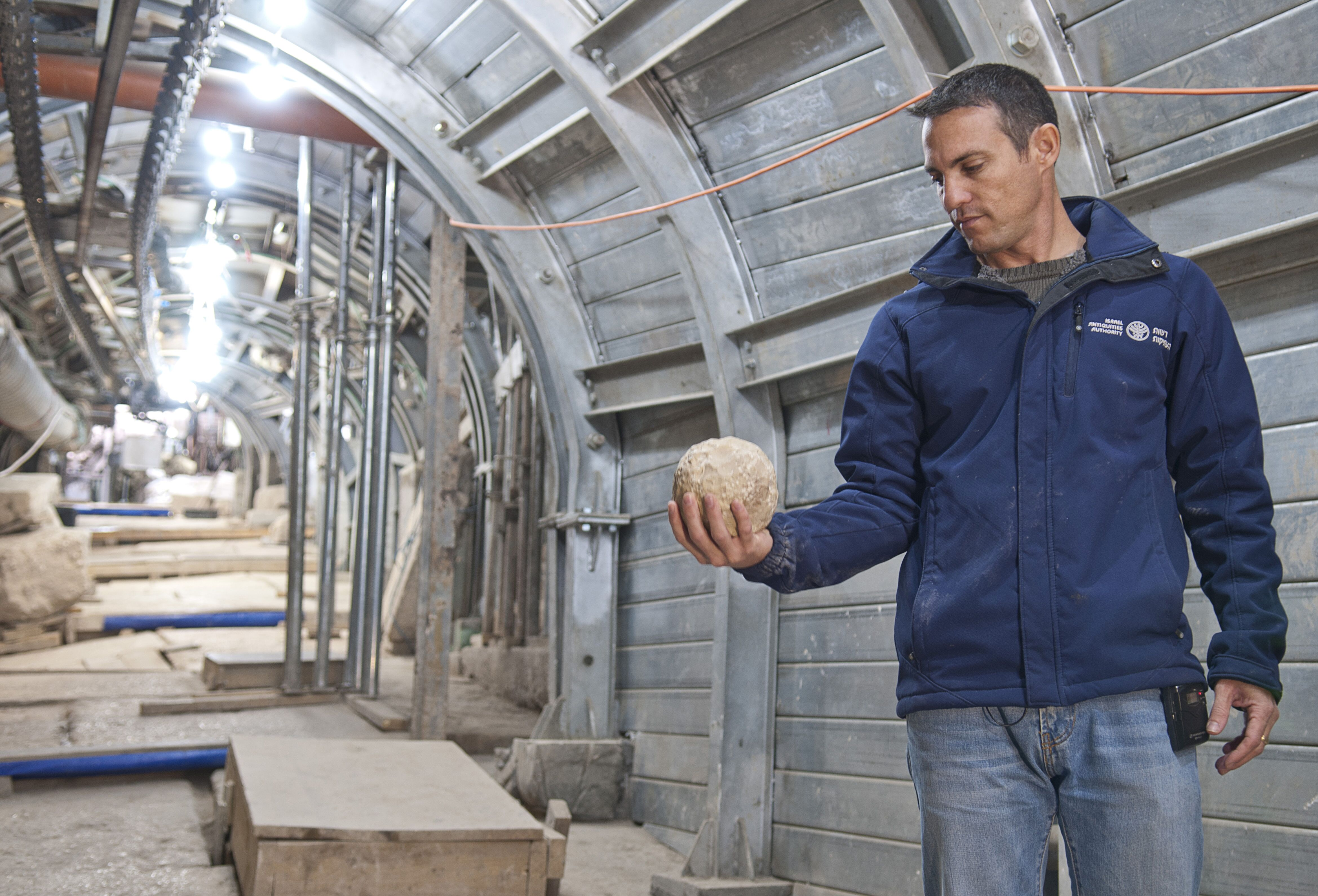 נחשון זנטון, ממנהלי חפירת הרחוב, מחזיק אבן בליסטרה שסביר כי שמשה בקרב במהלך המרד הגדול. צילום: שי הלוי