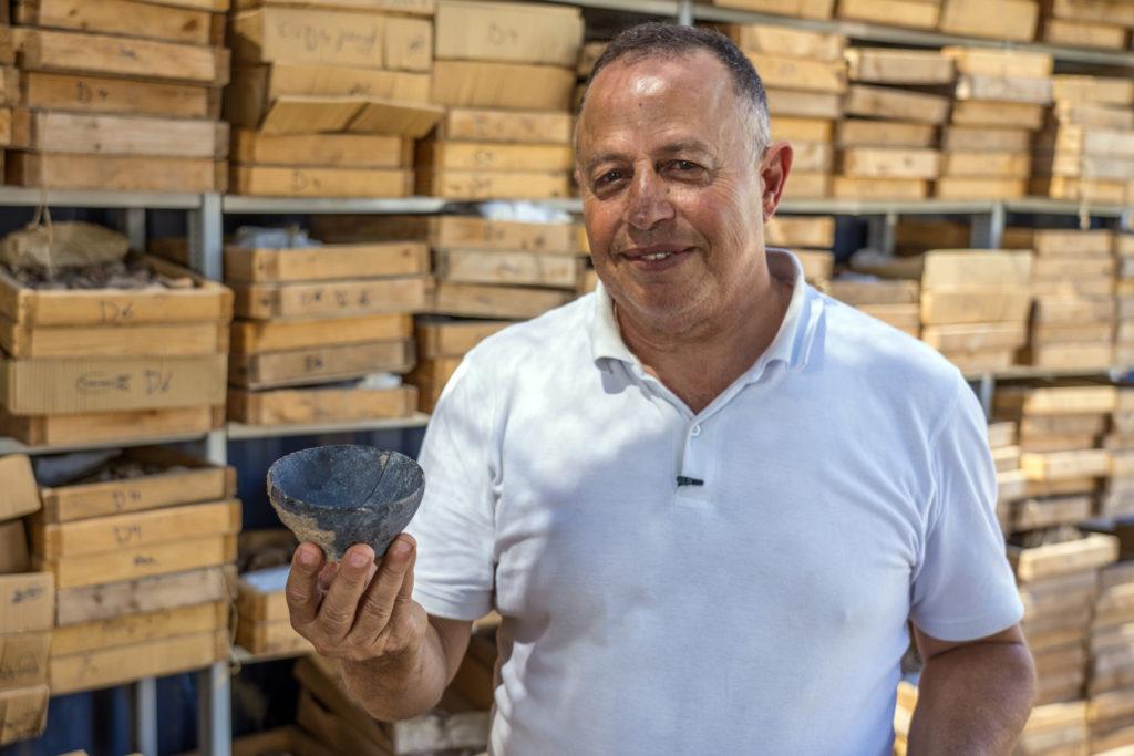 """ד""""ר חמודי חלאילה, מנהל החפירה מטעם רשות העתיקות, מחזיק קערית מהתקופה הניאוליתית. צילום: יניב ברמן"""