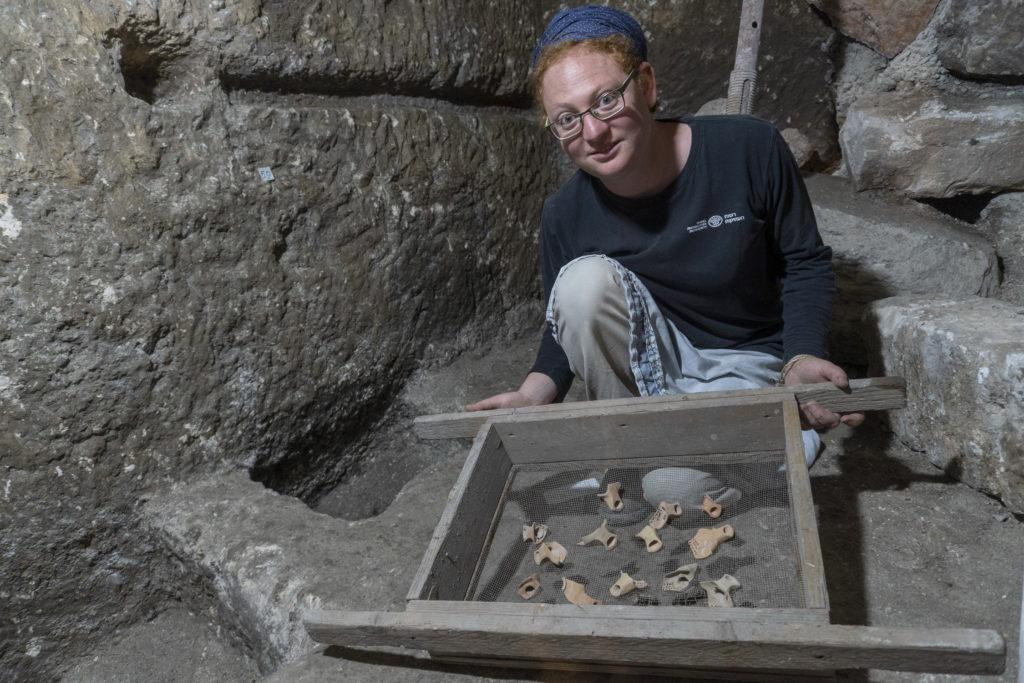 תהילה שדיאל, מנהלת החפירה, עם שברי נרות חרס מתקופת בית שני שנחשפו בתוך המערכת התת קרקעית. צילום: שי הלוי