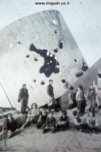 מגדל המים שקרס ובסמוך אנשי הקיבוץ החוזרים - צילום רפרודוקציה