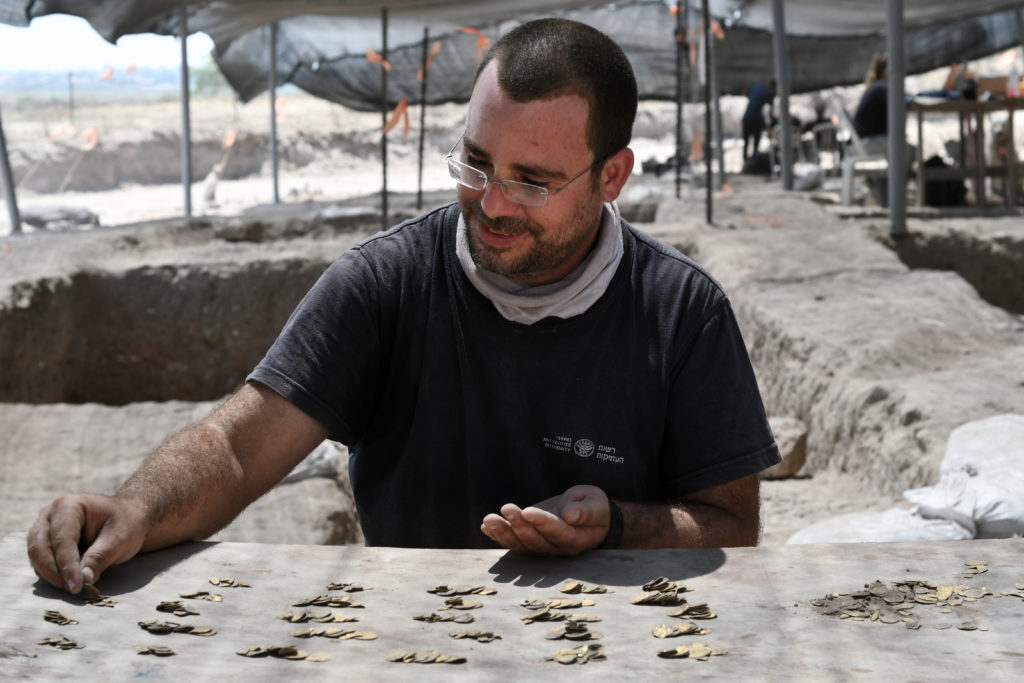 שחר קריספין, מומחה מטבעות ברשות העתיקות, סופר את מטבעות הזהב שנחשפו. צילום: יולי שוורץ