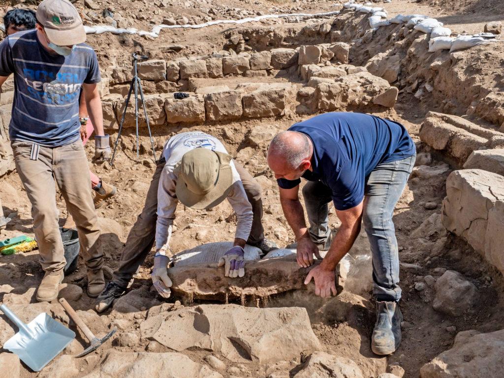 פועלים מרימים את אבן הגבול שהתגלת בנפח. צילום אסף פרץ רשות העתיקות