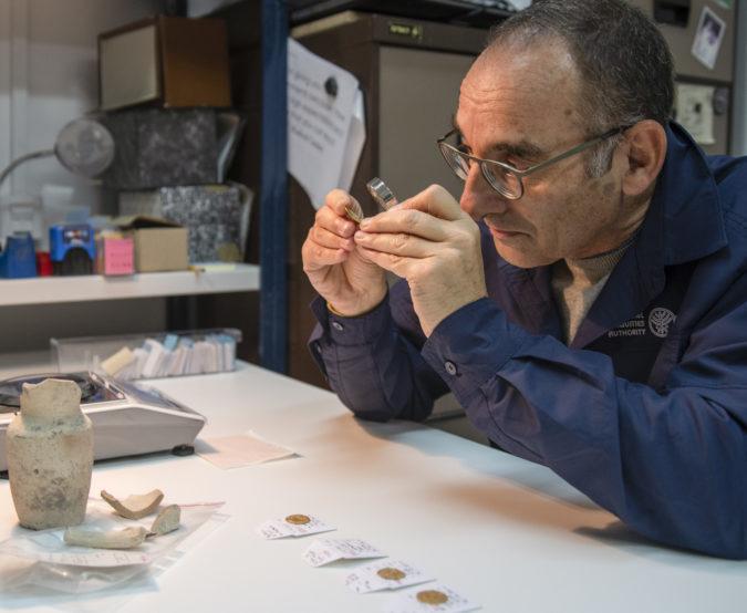 דר' רוברט קול בוחן את אחד המטבעות שנמצאו בפכית. צילום שי הלוי רשות