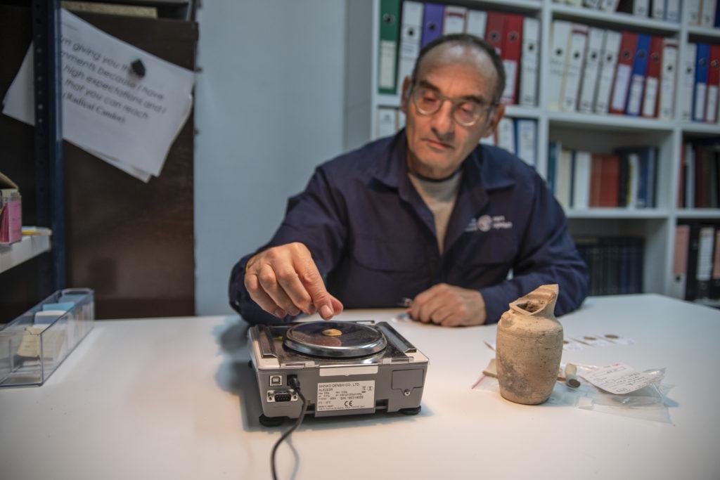 דר' רוברט קול מרשות העתיקות שוקל את אחד המטבעות שנמצאו בפכית. צילום שי הלוי רשות העתיקות