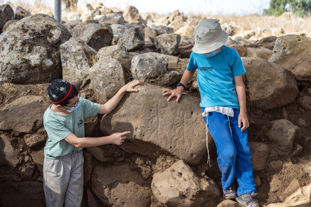 ילדים מחיספין המתנדבים בחפירה, מצביעים על הדמויות שחרותות על האבן. צילום: יניב ברמן