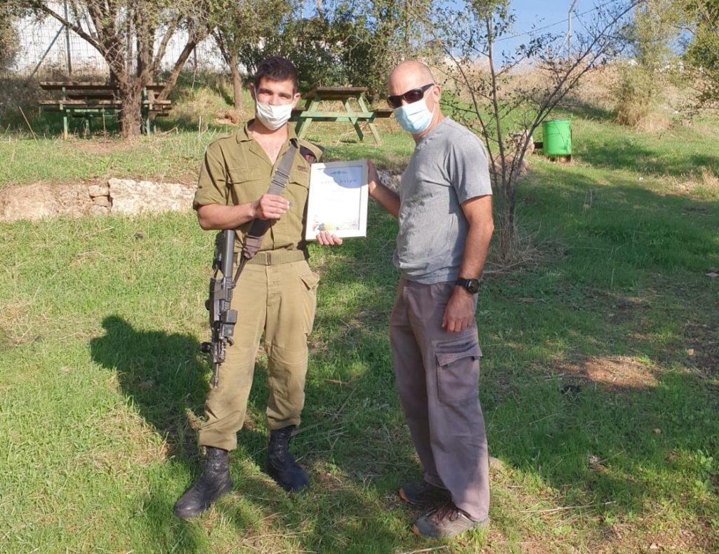 החייל עידו גרדי מקבל תעודת הוקרה על אזרחות טובה מניר דיסטלפלד, פקח היחידה למניעת שוד ברשות העתיקות באזור הצפון. צילום: רשות העתיקות