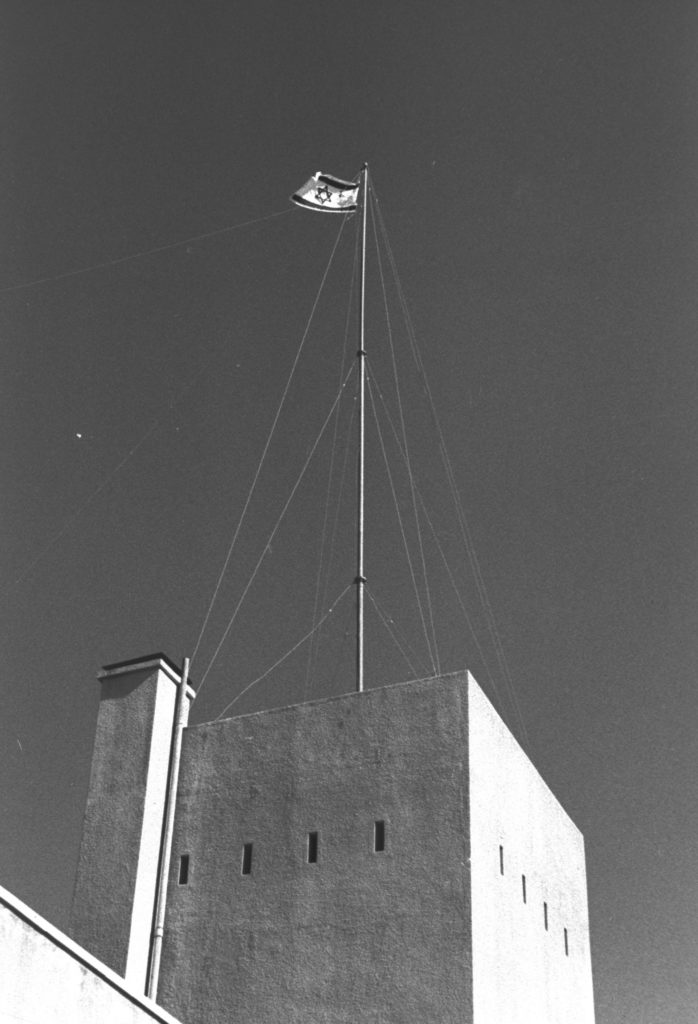 """דגל ישראל מונף על מצודת הטיגארט של משטרת תרשיחא במלחמת העצמאות 1.10.1948 - צילום: אלדן דוד , באדיבות ארכיון לע""""מ"""