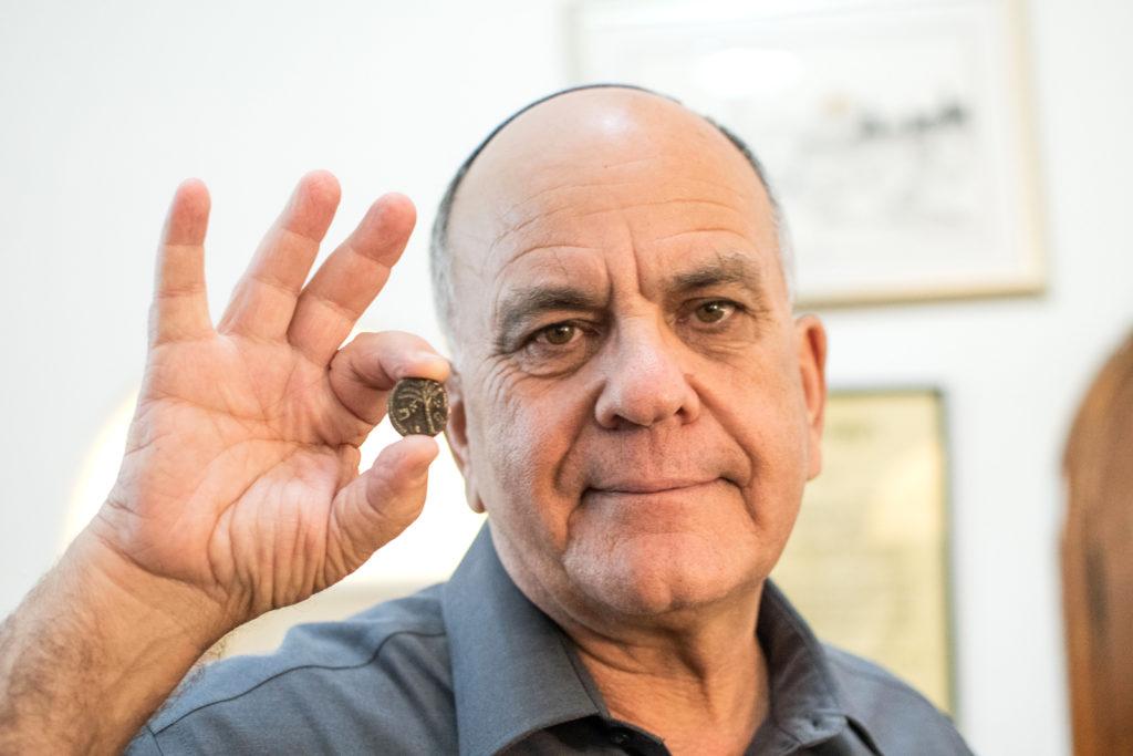 מנהל רשות העתיקות אלי אסקוזידו עם המטבע שיטוס לחלל. צילום יולי שוורץ