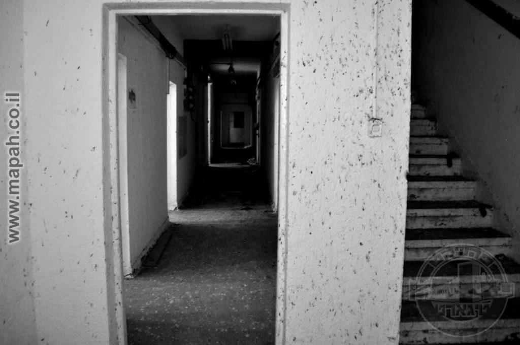 """מסדרון הבלוק המרכזי ממזרח למערב וגרם המדרגות העולה לחדרי המגורים בקומה השניה. בעת השימוש של צה""""ל, שימש למשרדים. - צילום: אפי אליאן"""